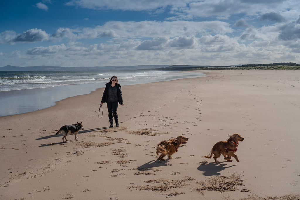 running around with three dogs on Lossiemouth Beach near inverness Scotland